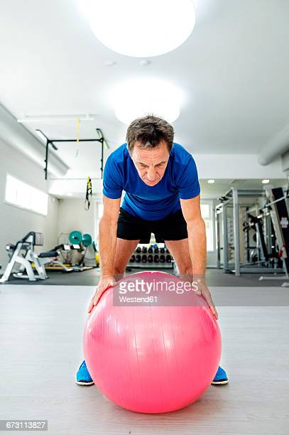 Senior man with fitness ball in gym