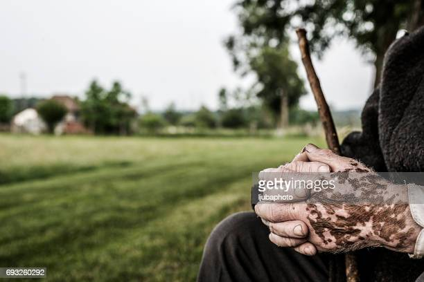 Senior  man with folded hands - focus on the weathered hands