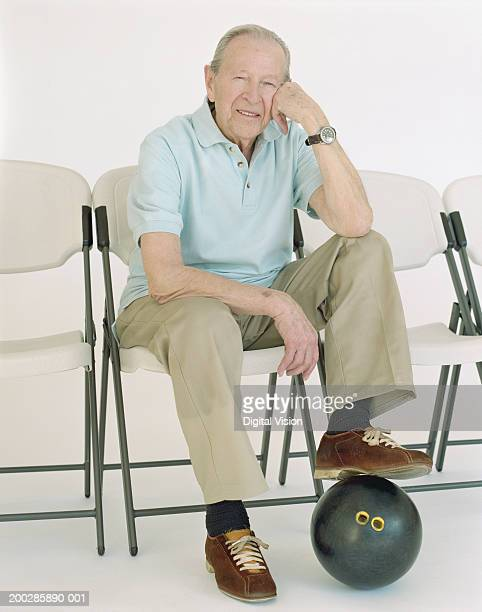 Senior man with foot on bowling ball, hand on cheek, portrait