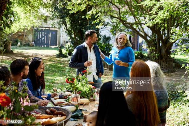 senior man with friend making a speech on a garden party - garden party stock pictures, royalty-free photos & images