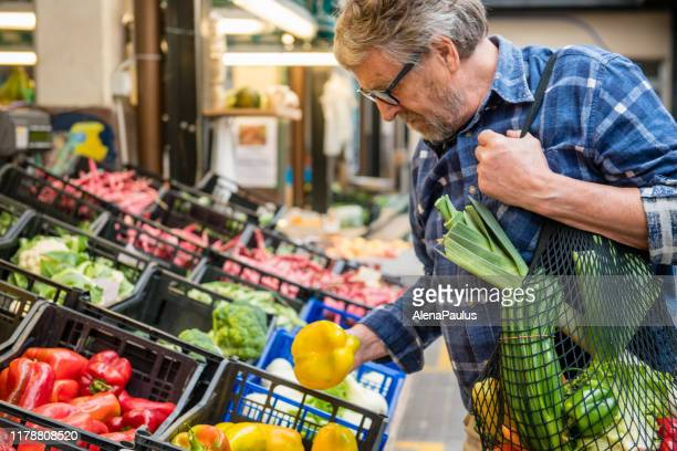 Senior Man with Fruits and Vegetables in a Black cotton mesh reusable bag, Zero Waste Shopping on Outdoors Market