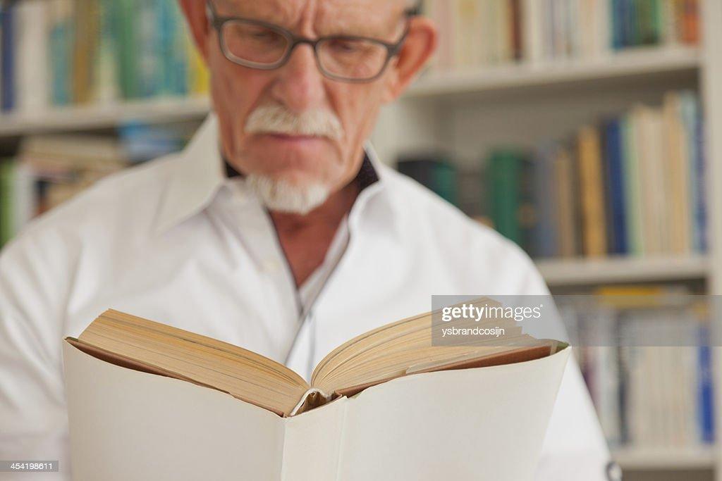 Homem idoso com óculos ler um livro na frente da estante. : Foto de stock