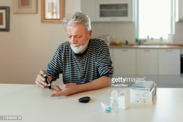 senior man with glucometer - lancet arch stock pictures, royalty-free photos & images