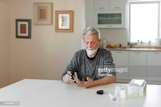 senior man with glucometer - glycemia stock pictures, royalty-free photos & images