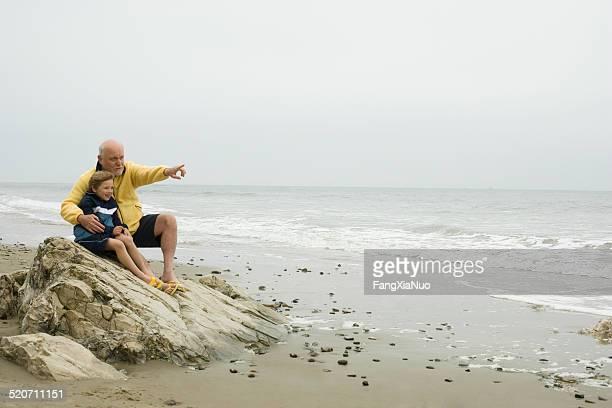 Alter Mann mit Enkel (8.) sitzt am Strand