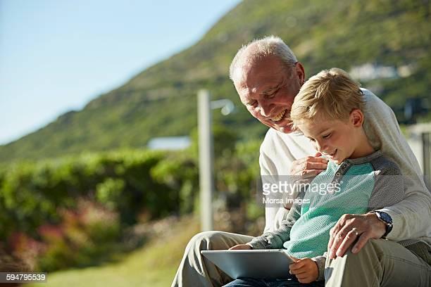 Senior man with grandson using digital tablet