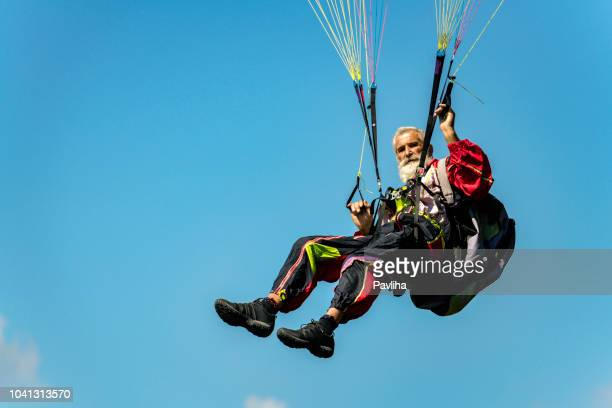 senior man with gray long beard paragliding in julian alps, primorska region in slovenia, europe - exhilaration stock photos and pictures