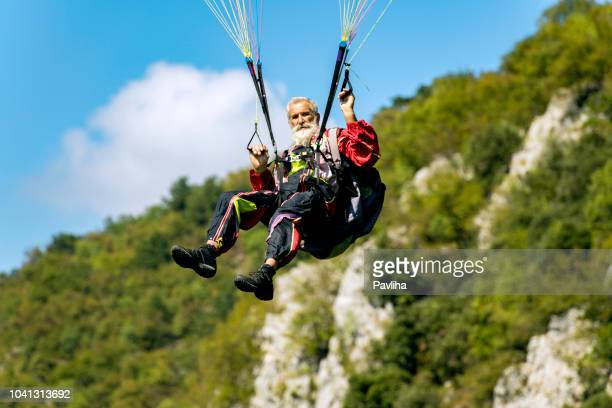 senior man with gray long beard paragliding in julian alps, primorska region in slovenia, europe - gliding stock pictures, royalty-free photos & images