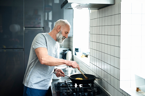 Senior man with grey beard using frying pan in modern kitchen - gettyimageskorea