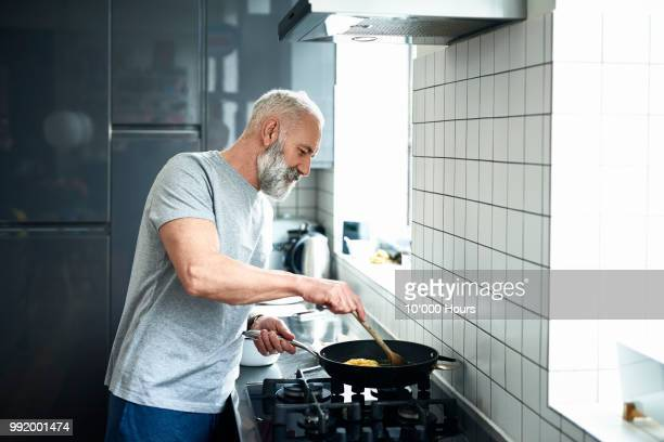 senior man with grey beard using frying pan in modern kitchen - estilo de vida imagens e fotografias de stock