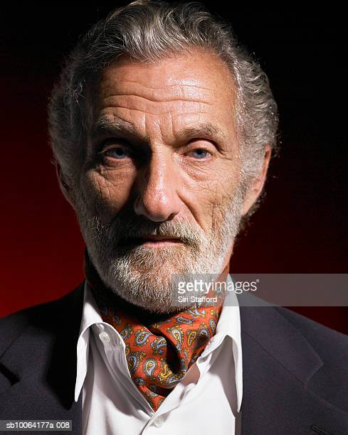 Senior man with grey hair and gray beard wearing red ascot and blue jacket, portrait, close-up