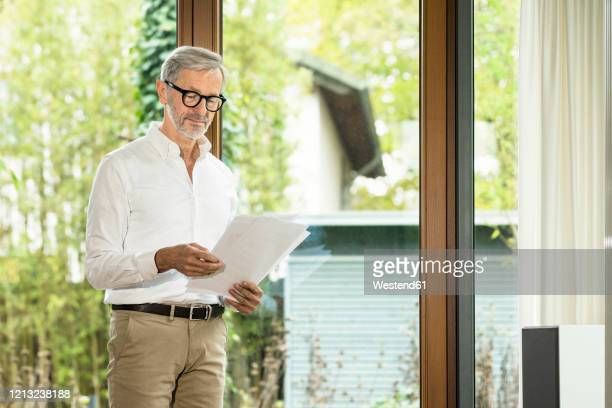 senior man with grey hair in modern design living room standing at window reading papers in home office - mann 60 jahre stock-fotos und bilder