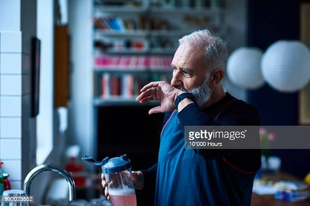 senior man with grey hair wiping mouth and drinking health shake - thirsty stock pictures, royalty-free photos & images