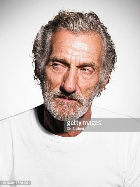 Senior man with greyhair and beard wears white t-shirt, close-up