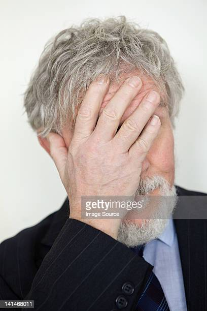 Senior man with hand covering face