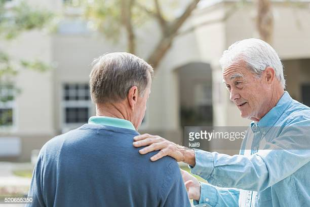 senior man with hand on his friend's shoulder - hand on shoulder stock pictures, royalty-free photos & images