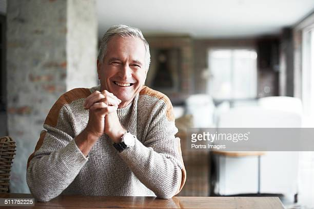 Senior man with hands clasped in house