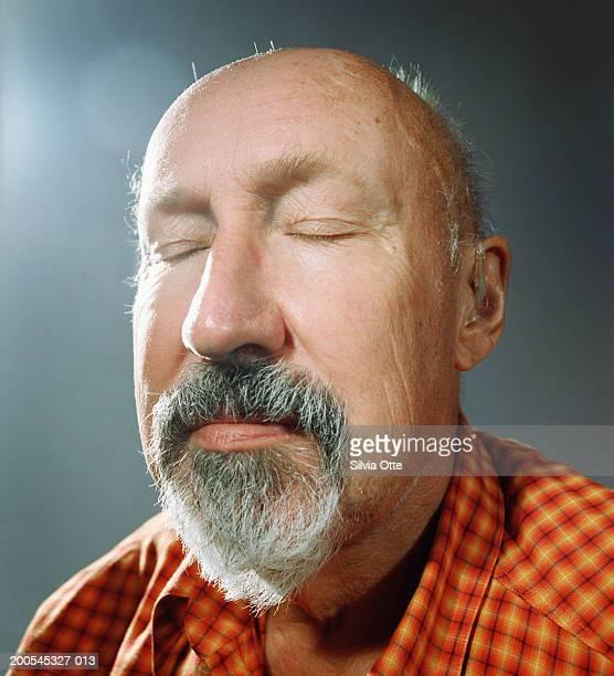 Senior man with hearing aid, eyes closed, close-up
