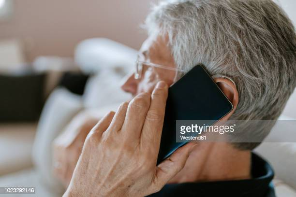 senior man with hearing aid on cell phone - ear stock pictures, royalty-free photos & images