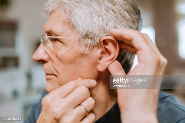 senior man with hearing aid - hearing aid stock pictures, royalty-free photos & images