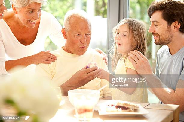 Senior man with his family blowing out birthday candle