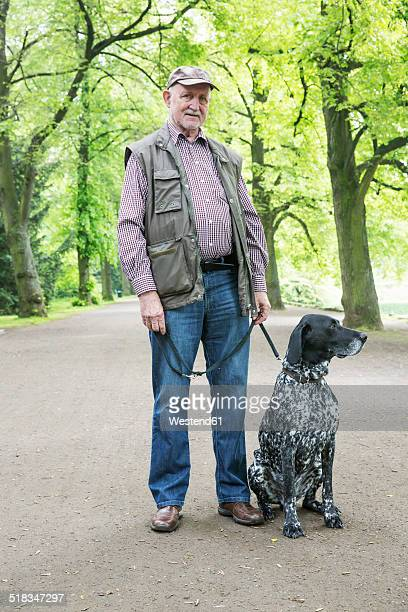 senior man with his german shorthaired pointer in city park - pointer dog stock pictures, royalty-free photos & images