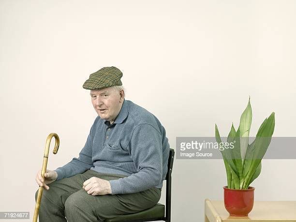 senior man with houseplant - flat cap stock pictures, royalty-free photos & images