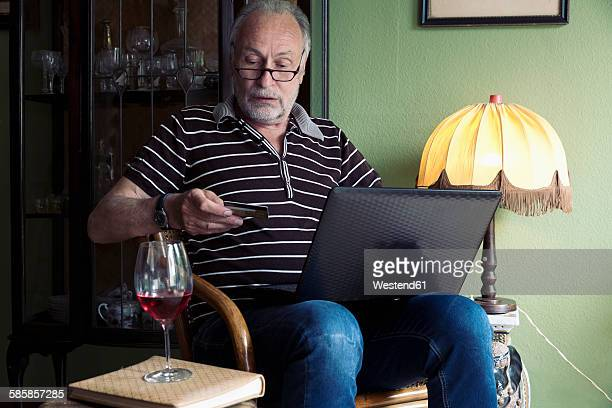 Senior man with laptop and credit card at home