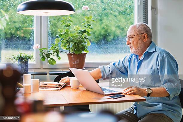 Senior man with laptop reaching for newspaper at table