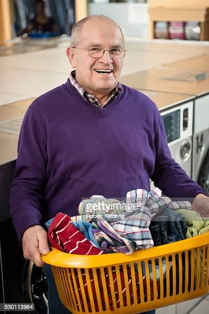 Senior man with laundry, smiling
