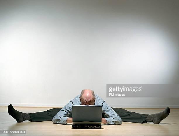 senior man with legs stretched outward on floor using laptop - split acrobatiek stockfoto's en -beelden