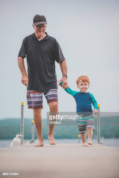 senior man with little boy at the lake, summer day - lake auburn stock photos and pictures