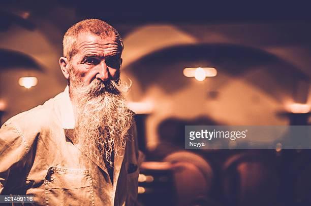 alter mann mit langem bart stehen in einem wein-store - produzent stock-fotos und bilder