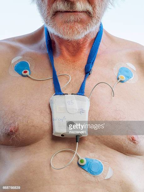 Senior man with long-term ECG on his chest, close up