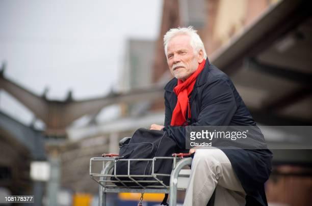 Uomo anziano con carrello bagagli presso la Stazione ferroviaria