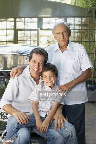 Senior man with man and young boy outdoors leaning on car smiling