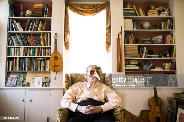 Senior man with Mardi Gras Mask Seated in front of window