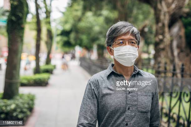 senior man with mask walking on the street - surgical mask stock pictures, royalty-free photos & images