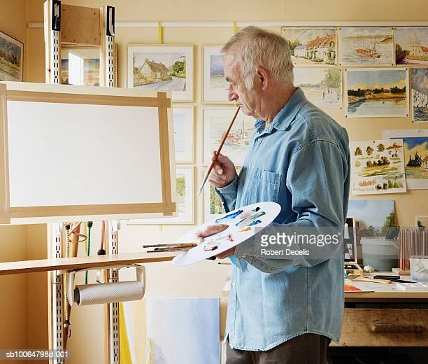 senior man with palette, looking at canvas in studio - einzelner senior stock-fotos und bilder