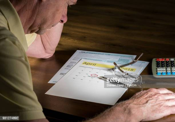 Senior Man With Pen And Calendar On Table