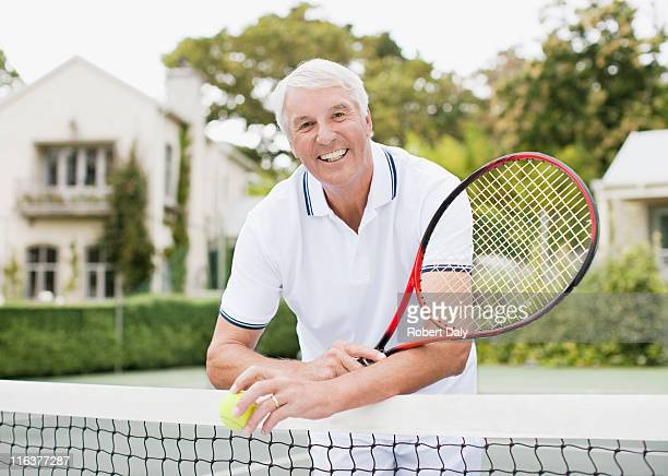 Senior man with racket and ball on tennis court