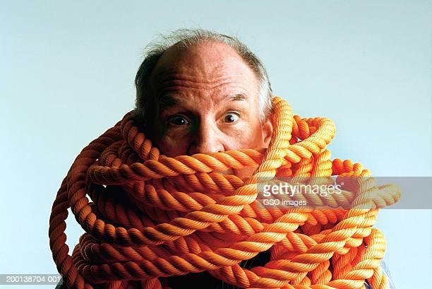 senior man with rope wrapped around shoulders and neck, portrait - mann gefesselt stock-fotos und bilder