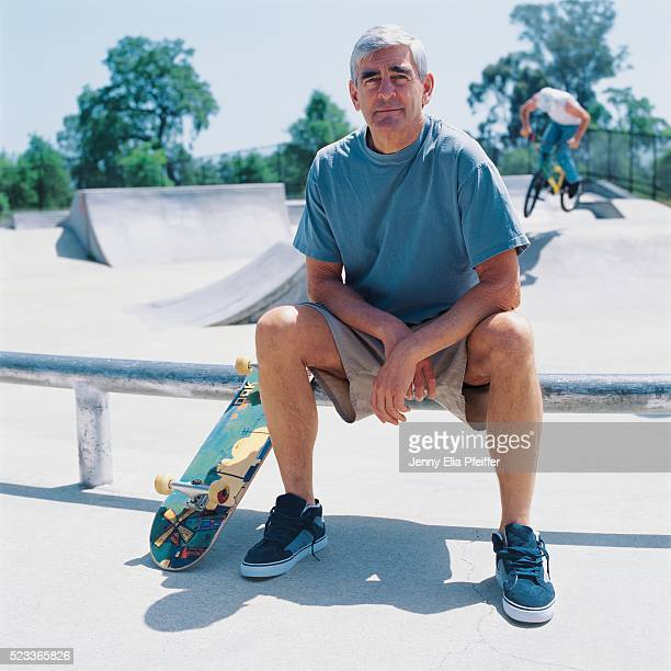 Senior man with skateboard in skateboard park