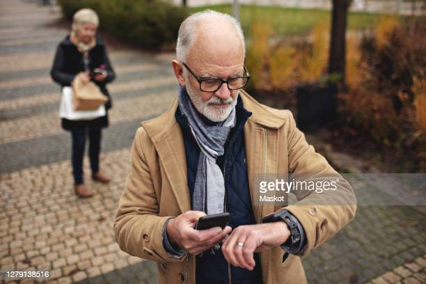 senior man with smart phone checking the time while partner standing behind on footpath - smart watch stock pictures, royalty-free photos & images