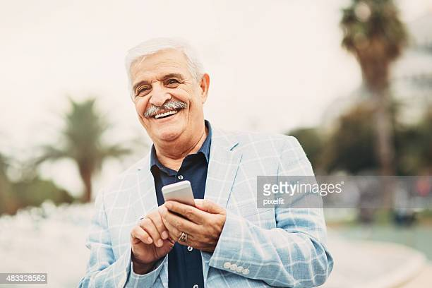 Senior man with smart phone smiling outdoors
