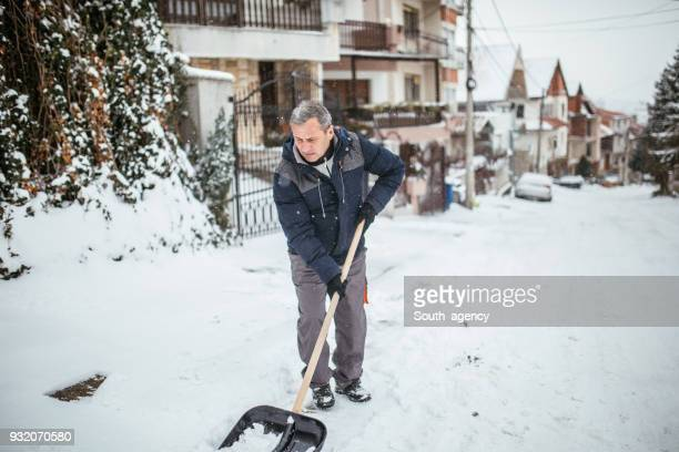 senior man with snow shovel cleans sidewalk - digging stock pictures, royalty-free photos & images