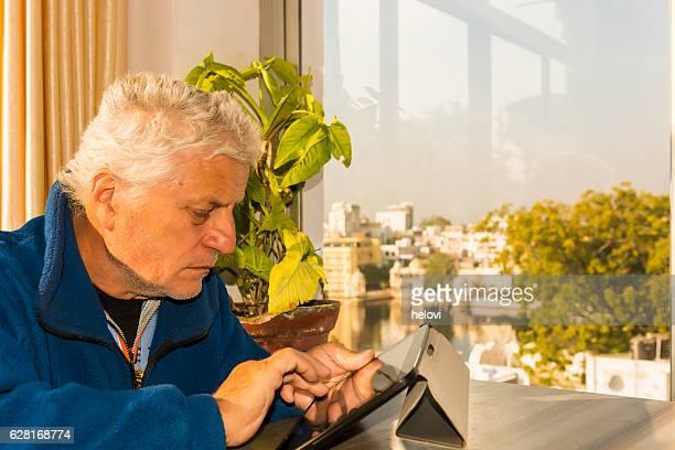 Senior man with tablet at the Lake Pichola