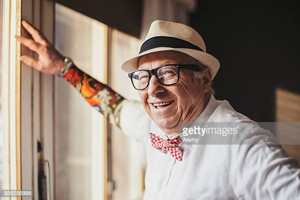 senior man with tattoo smiling and looking at camera - tattoo stock pictures, royalty-free photos & images