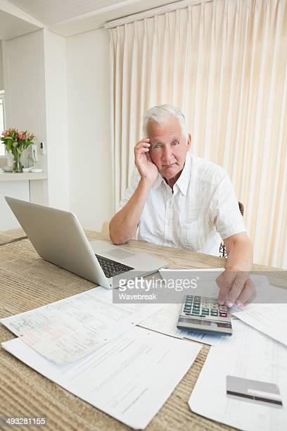 Homem idoso com impostos documentos e portátil em casa
