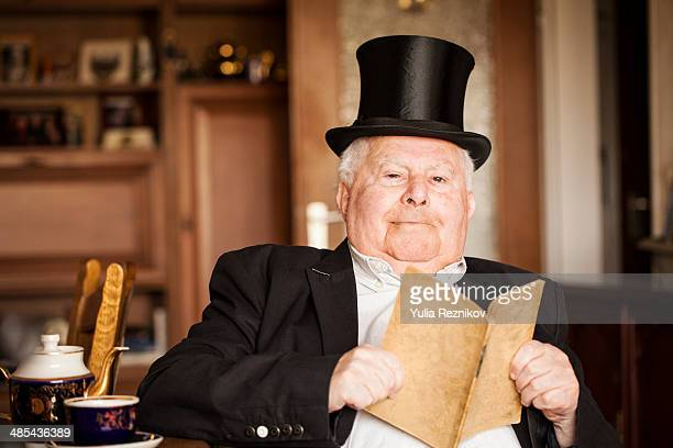 senior man with top hat and tail coat reading book - tail coat stock pictures, royalty-free photos & images